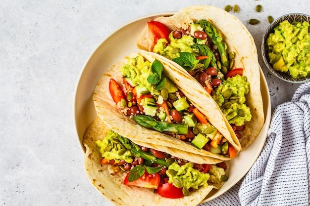 Wegańskie tortille z quinoą, szparagami, fasolą, warzywami i guacamole.