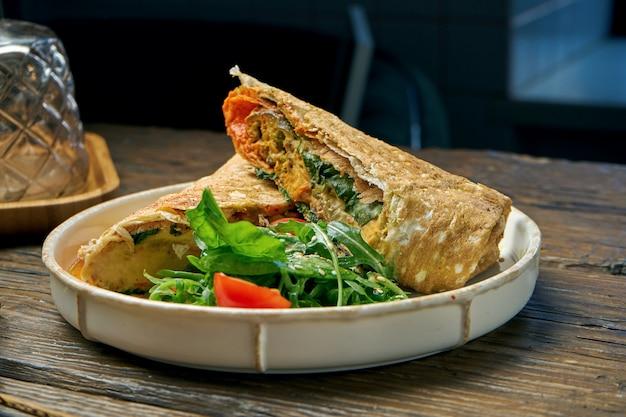 Wegetariańska bułka shawarma ze szpinakiem, pomidorami, hummusem i roztopionym serem w talerzu na drewnianym