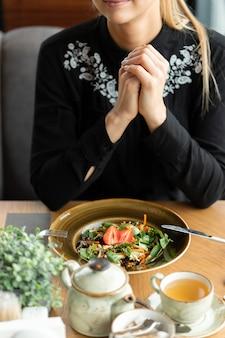Wegetariańska dziewczyna je w kawiarni. zdrowa warzywna sałatka z bazylią i orzechami, przyozdobiona świeżymi truskawkami. filiżanka zielonej herbaty i czajnik. niewielka głębokość pola, rozmyte tło.