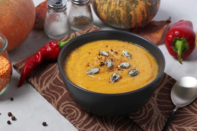 Wegetariańska jesień kremowa zupa dyniowa z czerwoną soczewicą na ciemnym talerzu. zbliżenie. format poziomy.