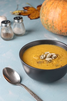 Wegetariańska jesień kremowa zupa dyniowa z nasionami na jasnoniebieskim tle, orientacja pionowa