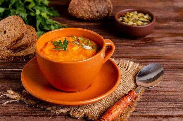 Wegetariańska jesienna zupa krem z dyni i marchewki z nasionami i natką pietruszki na drewnianej powierzchni z miejsca kopiowania, płasko leżał