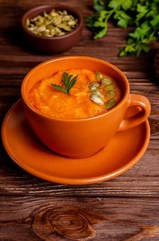 Wegetariańska jesienna zupa krem z dyni i marchewki z nasionami i pietruszką na drewnianym stole