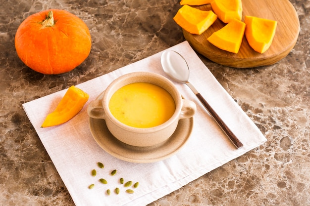 Wegetariańska jesienna zupa krem z dyni z pestkami dyni na talerzu zupy.