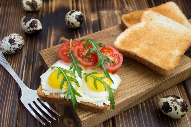 Wegetariańska kanapka z jajkiem przepiórczym, wiśnią i rukolą na drewnianej desce do krojenia