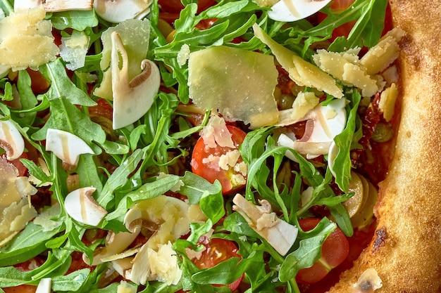 Wegetariańska pizza opalana drewnem z rukolą, warzywami i parmezanem na desce. selektywne skupienie