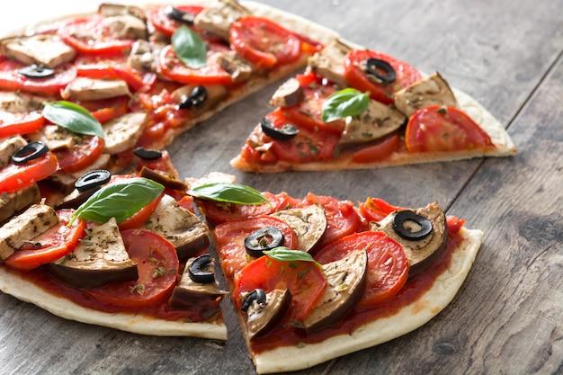 Wegetariańska pizza z bakłażanem, pomidorem, czarnymi oliwkami, oregano i bazylią na drewnianej powierzchni