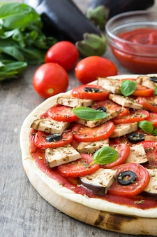 Wegetariańska pizza z bakłażanem, pomidorem, czarnymi oliwkami, oregano i bazylią na drewnianym stole