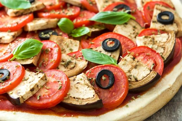Wegetariańska pizza z bakłażanem, pomidorem, czarnymi oliwkami, oregano i bazylią na drewnianym stołu zakończeniu up