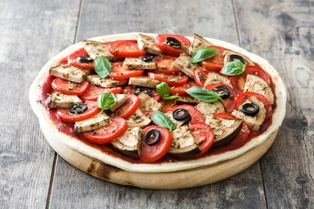 Wegetariańska pizza z bakłażanem, pomidorem, czarnymi oliwkami, oregano i bazylią