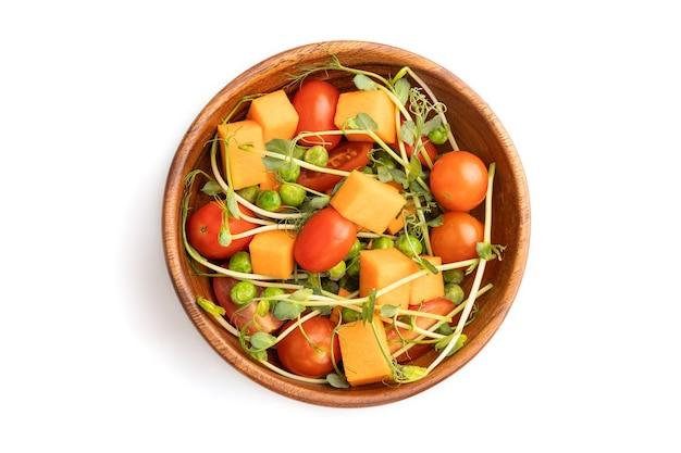 Wegetariańska sałatka jarzynowa z pomidorów, dyni, kiełków groszku microgreen na białym tle