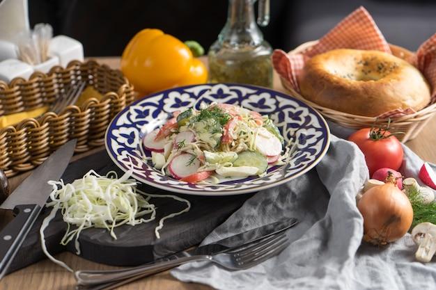 Wegetariańska sałatka jarzynowa z rzodkiewki i śmietany w talerzu z tradycyjnym uzbeckim