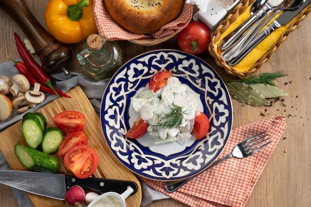 Wegetariańska sałatka jarzynowa z rzodkiewki, ogórków i pomidorów doprawiona kwaśną śmietaną w talerzu z tradycyjnym uzbeckim