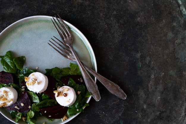 Wegetariańska sałatka z buraków ze szpinakiem, kozim serem i różnymi orzechami na talerzu ceramicznym. dieta, zdrowa, przekąska, koncepcja obiadu posiłek. na rustykalnym tle. widok z góry. płaskie ułożenie
