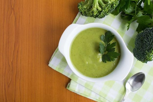 Wegetariańska zupa brokułowa puree w białej misce na jasnobrązowym drewnianym