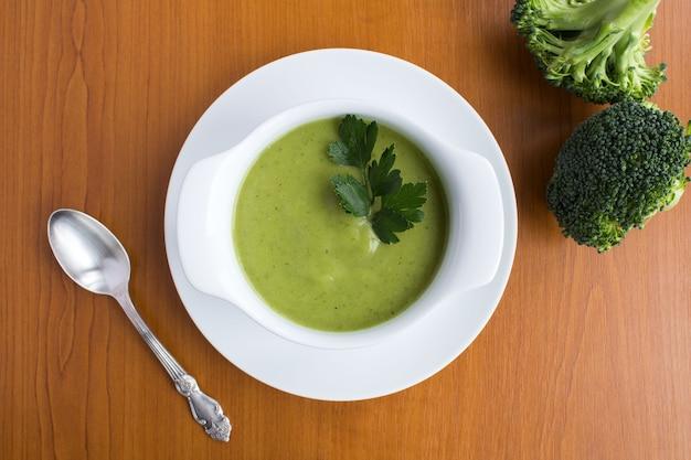Wegetariańska zupa brokułowa puree w białej misce na jasnobrązowym tle drewniane widok z góry