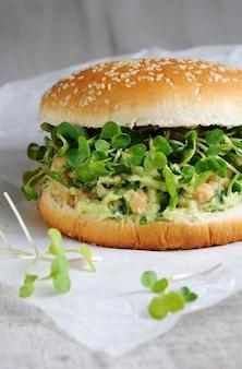 Wegetariański burger z bułki bezglutenowej z awokado z ciecierzycy i kiełkami rzodkiewki z ziołami