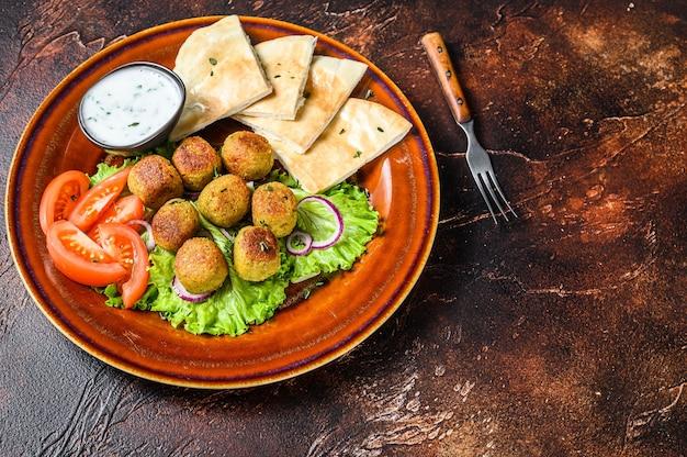 Wegetariański falafel z chlebem pita, świeżymi warzywami i sosem na talerzu