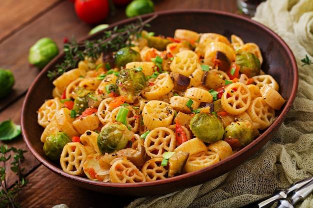 Wegetariański makaron warzywny rocchetti z brukselką, pomidorem, bakłażanem i papryką w brązowej misce na drewnianym stole