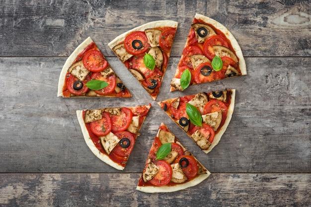 Wegetariański plasterek pizzy z bakłażanem, pomidorem, czarnymi oliwkami, oregano i bazylią na drewnianej powierzchni
