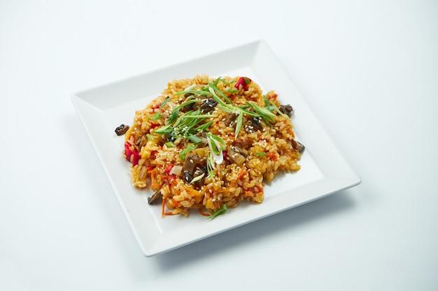 Wegetariański ryż w woku w sosie słodko-kwaśnym z warzywami w białym talerzu na szarym stole