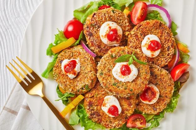 Wegetariańskie burgery, paszteciki z roślin strączkowych, cebuli i zieleniny w panierce z bułki tartej panko podane na białym talerzu ze świeżą sałatą i sosem pomidorowym, widok poziomy z góry, leżąc na płasko, zbliżenie