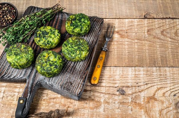 Wegetariańskie burgery warzywne z ziołami na desce.