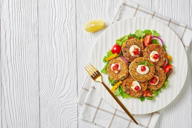 Wegetariańskie burgery z roślin strączkowych, cebuli i zieleniny w panierce z bułki tartej panko podane na białym talerzu ze świeżą sałatą i cytryną, widok poziomy z góry, płasko leżący, wolna przestrzeń
