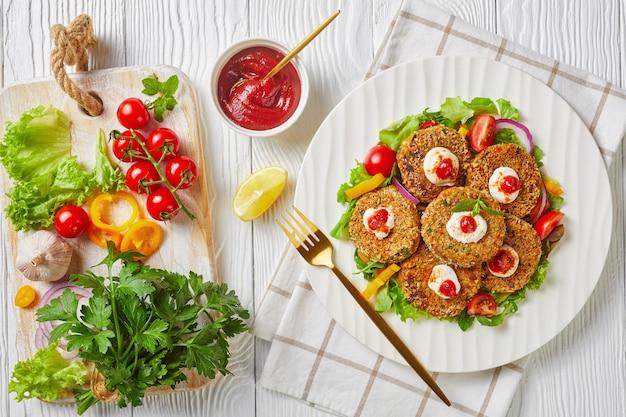 Wegetariańskie burgery z roślin strączkowych, cebuli i zieleniny w panierce z bułki tartej panko podane na białym talerzu ze świeżą sałatą i sosem pomidorowym, widok poziomy z góry, płasko leżący, wolna przestrzeń