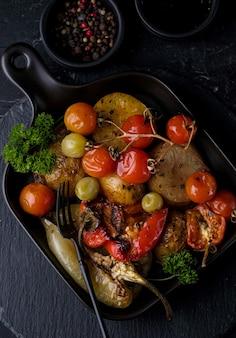Wegetariańskie danie z grillowanych warzyw na czarnej patelni