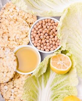 Wegetariańskie jedzenie na jasnym tle. kapusta pekińska, orzech włoski, ciecierzyca, rośliny strączkowe, oliwa z oliwek, cytryna, pieczywo chrupkie.