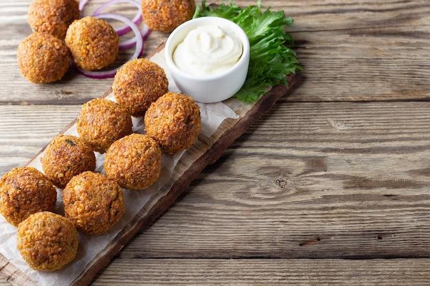 Wegetariańskie kulki falafel z ciecierzycy na drewnianej rustykalnej desce tradycyjne arabskie jedzenie ciemne tło
