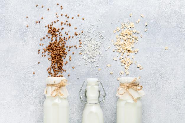 Wegetariańskie mleko dietetyczne z płatków ryżowych, gryki i owsa, trzy rodzaje domowej roboty na szarym betonowym stole. pojęcie zdrowej diety. skopiuj miejsce. widok z góry.