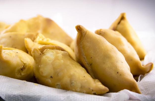 Wegetariańskie samosas wypełnione ziemniaczanym i zielonym groszkiem. indyjskie specjalne tradycyjne jedzenie uliczne