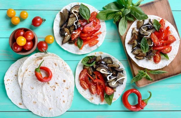 Wegetariańskie tacos z bakłażanem, pomidorkami koktajlowymi, słodką papryką na jasnym drewnianym stole