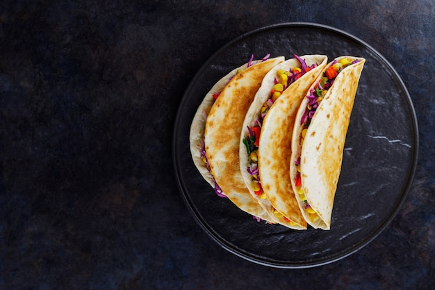 Wegetariańskie tacos z kukurydzą, fioletową kapustą i pomidorami na czarnym talerzu. tacos z warzywami i sosem guacamole na ciemnym tle. skopiuj miejsce. widok z góry
