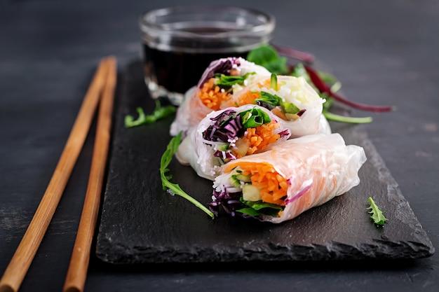 Wegetariańskie wietnamskie sajgonki z pikantnym sosem, marchewką, ogórkiem, czerwoną kapustą i makaronem ryżowym.