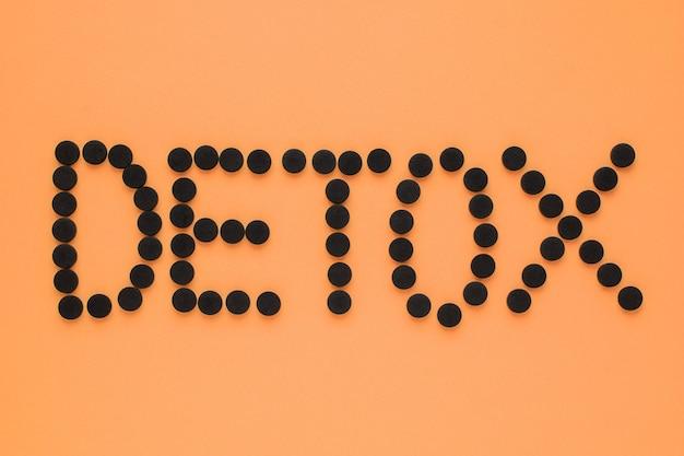 """Węgiel aktywowany medycznie w postaci napisu """"detox"""" na pomarańczowym tle."""