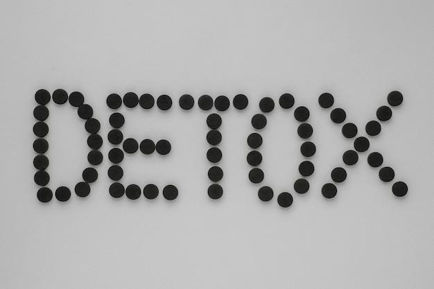 """Węgiel aktywowany medycznie w postaci napisu """"detox"""" na szarym tle."""