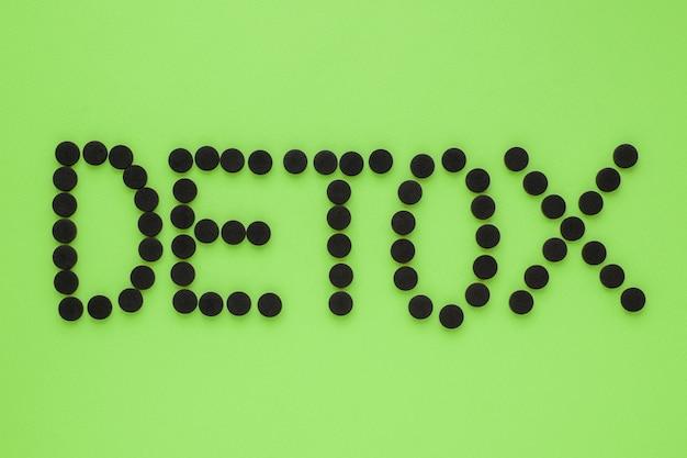 """Węgiel aktywowany medycznie w postaci napisu """"detox"""" na zielonej powierzchni. widok z góry, miejsce"""