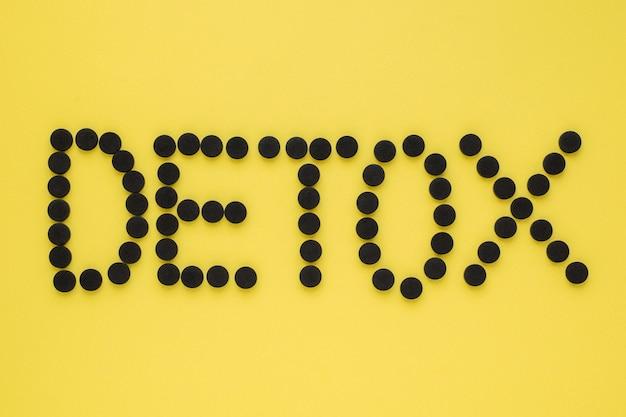 """Węgiel aktywowany medycznie w postaci napisu """"detox"""" na żółtej powierzchni. widok z góry, miejsce"""