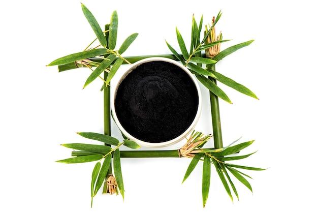 Węgiel bambusowy, zielone liście i proszek na białym tle. widok z góry, leżał płasko.