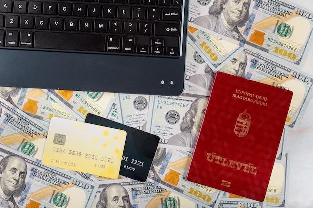 Węgierskie paszporty kupują bilety online za pomocą kart kredytowych na klawiaturze laptopa na banknotach w dolarach amerykańskich