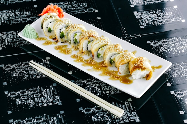 Węgorzowe rolki sushi z zieloną papryką przyozdobioną sezamem