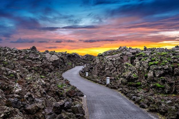Wejście do blue lagoon ze skałami lawy i zielonym mchem o zachodzie słońca na islandii.