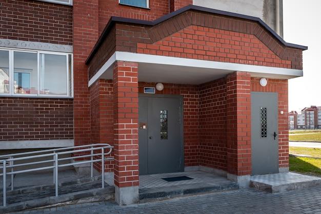 Wejście do budynku mieszkalnego z metalowymi drzwiami z domofonem.