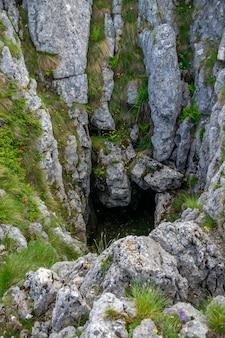 Wejście do ciemnej jaskini wśród gór.