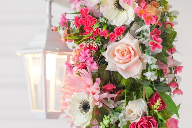 Wejście do domu z białą lampą i kwiatem