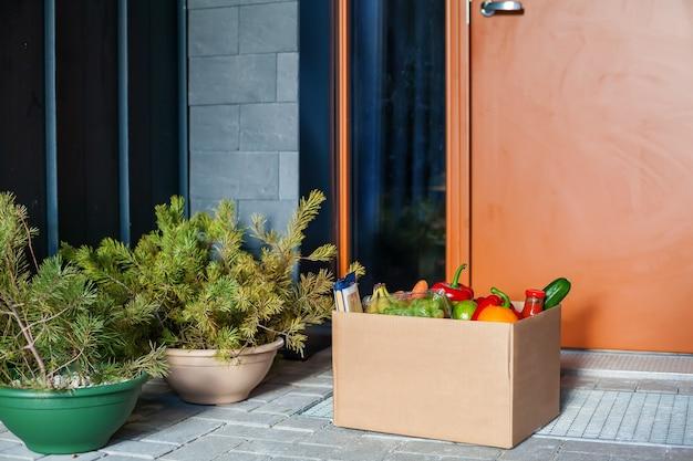 Wejście do domu z dostarczonym pudełkiem z jedzeniem. bezkontaktowa dostawa.