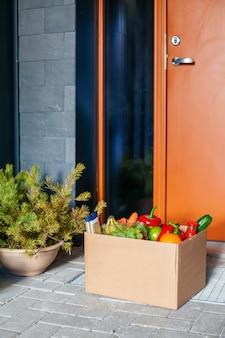 Wejście do mieszkania z dostarczonym pudełkiem z jedzeniem. bezkontaktowa dostawa.